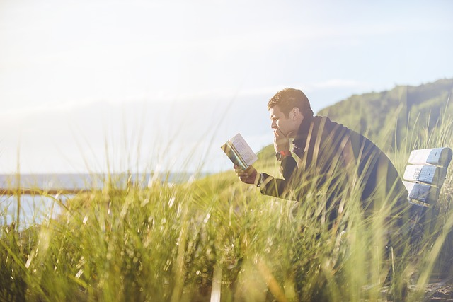 Photo of a man reading on a bench near a lake.