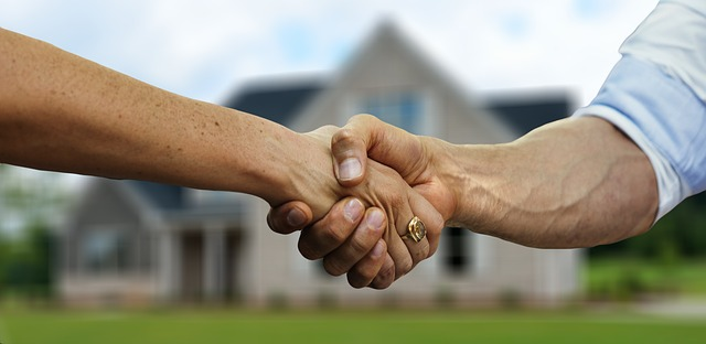 Two people shaking hands in front of a house.