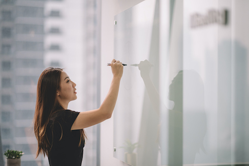 Asian female writing on white board with marker in conference room.