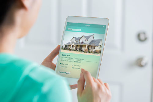 Woman uses tablet to view home listing