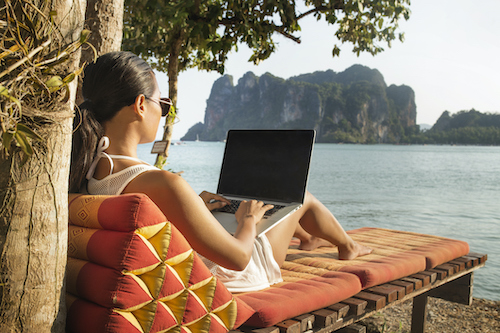 Woman using laptop computer while sitting on lounge chair against sea